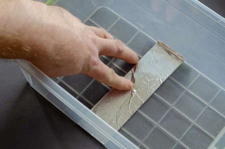 A man seals a crack in a plastic container with aluminum tape. The process of repairing a clear food container. View from above from an angle. Selective focus. Foto de archivo