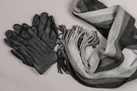 Wool scarf and leather gloves against a gray background. Knitted men's black and gray neck scarf. Warm casual wear accessories. Top view. Reklamní fotografie