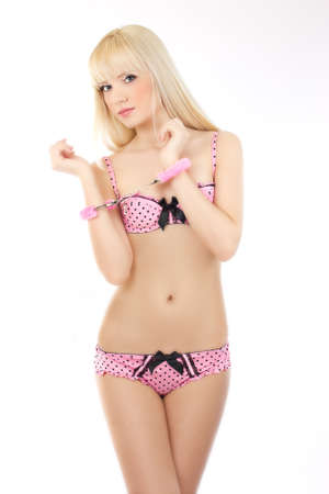 Sexy beautiful blonde girl in handcuffs wearing pink lingerie isolated on white background Stock Photo