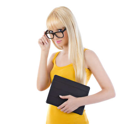 Pretty blonde woman looking over the top of her glasses while smiling holding tablet over white