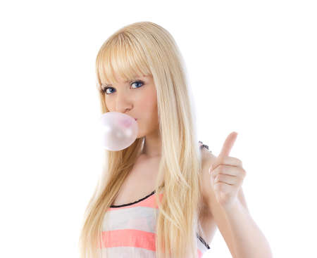 gums: Pretty woman giving thumbs up and blowing bubble with bubble gum over white Stock Photo