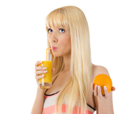 Portrait of pretty woman looking up and holding orange while sipping glass of juice over white photo