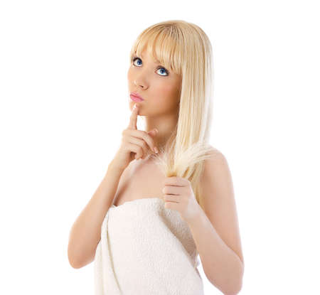 Beautiful blonde woman holding her hair and thinking over white