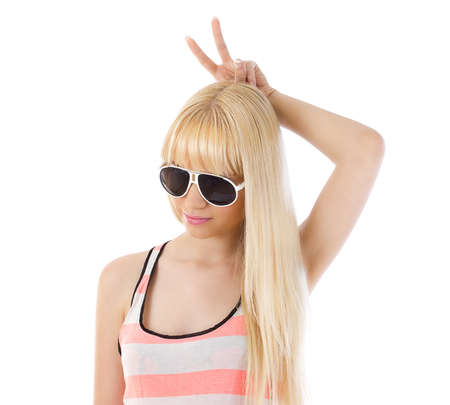 believable: Portrait of a pretty young woman wearing glasses using her fingers as bunny ears over white Stock Photo