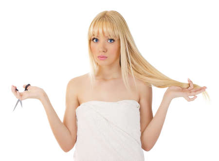 Blonde woman with scissors holding her hair and wondering over white photo
