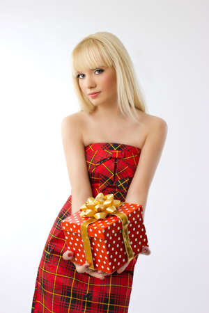 Beautiful young blonde girl holding christmas gift in red dress on grey background Stock Photo