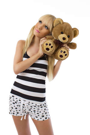 pink teddy bear: Beautiful blonde girl wearing pajamas embraces teddy bear on white background Stock Photo