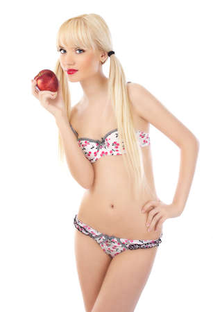 Seductive blonde woman in lingerie holding red apple on white background photo