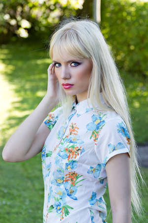 Portrait of a beautiful blonde woman in summer park