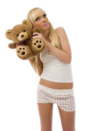 pijama: Chica rubia con Encanto en pijama abraza el oso de peluche sobre fondo blanco Foto de archivo