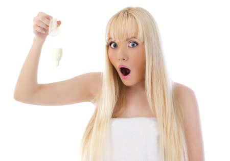 condones: Mujer sorprendida joven con condón sobre fondo blanco Foto de archivo