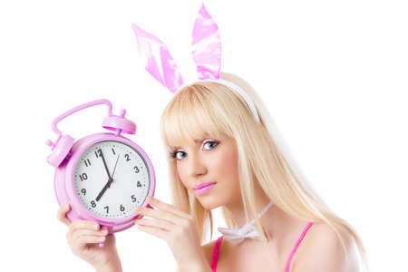 Beautiful girl in bunny ears holding pink clock on white background Stock Photo