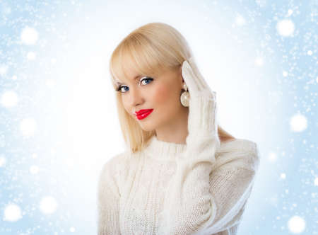 Beautiful woman in white sweater with red lips on a snow background photo
