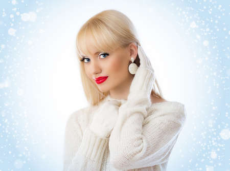 Beautiful woman in white sweater with red lips on a snow background Stock Photo - 16334416