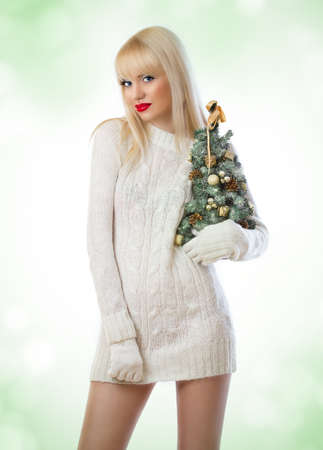 Beautiful blonde woman holding small christmas tree on green background photo