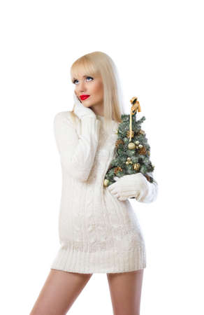 Beautiful woman holding small christmas tree and looking up at copyspace on white background Stock Photo - 16551551