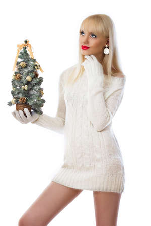 Blonde woman holding small christmas tree on white background photo