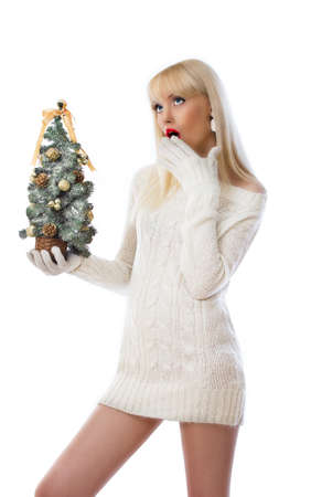 Woman holding small christmas tree and looking up at copyspace on white background Stock Photo - 16551555