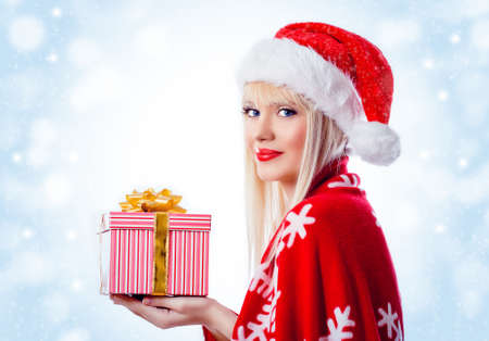 Beautiful blonde woman with christmas gift in red hat. Snow flakes Stock Photo - 16756273