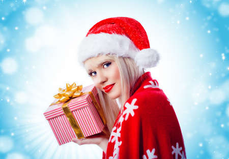 Pretty young blonde girl holding christmas gift in red hat Stock Photo - 16756283