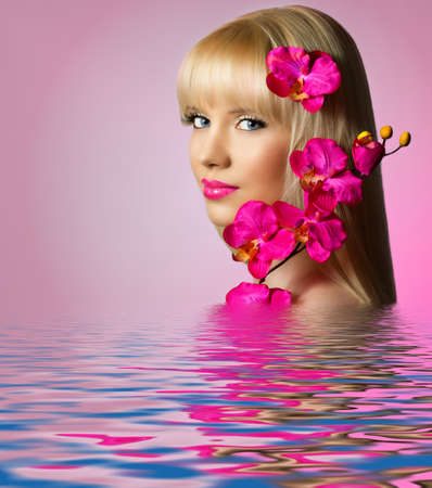 Beautiful blonde woman with orchid flowers in water