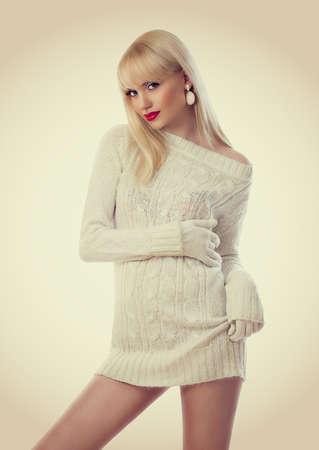 Beautiful blonde young woman in knitted dress  photo