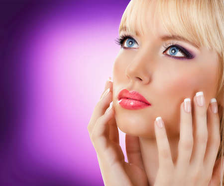 Beautiful blonde woman with manicure and purple makeup photo