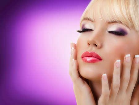 nail salon: Beautiful blonde woman with manicure and purple makeup Stock Photo