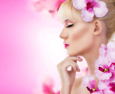 Beautiful blonde girl with flowers and perfect makeup photo