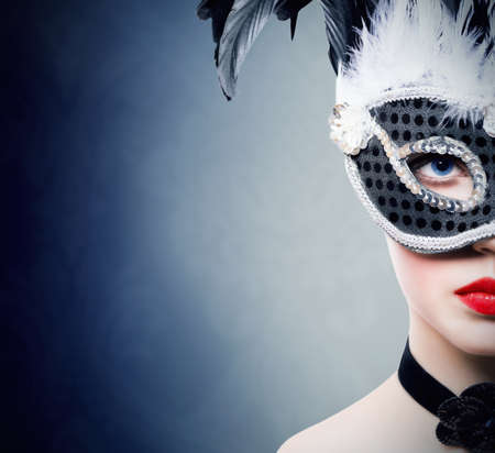 Beautiful young woman in black carnival mask photo