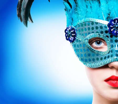 Beautiful young woman in blue carnival mask photo