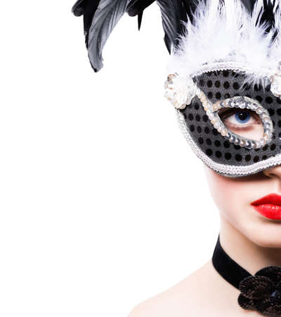 Beautiful young woman in black carnival mask on white background