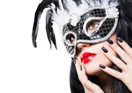 Beautiful young woman in black carnival mask with manicure on white background photo