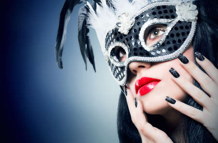 Beautiful young woman in black carnival mask with manicure