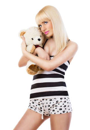 Beautiful blonde girl wearing pajamas embraces teddy bear on white background photo