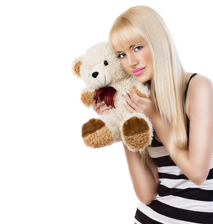 Beautiful blonde girl wearing pajamas embraces teddy bear on white background photo