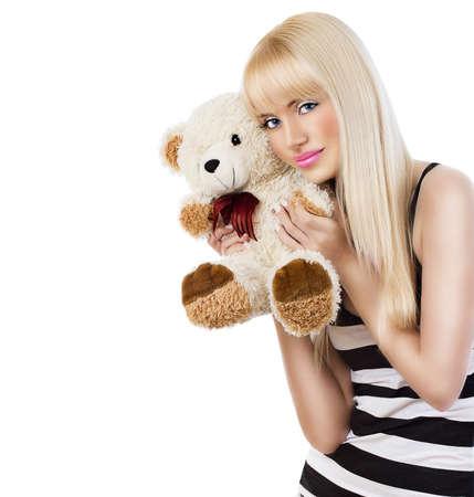 Beautiful blonde girl wearing pajamas embraces teddy bear on white background 版權商用圖片