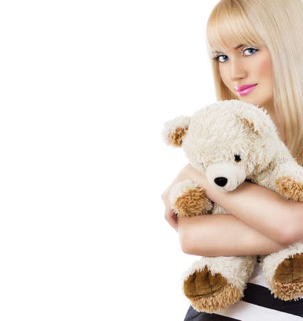 Beautiful blonde girl wearing pajamas embraces teddy bear on white background Stock Photo - 19358429