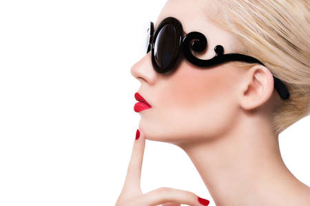 finger to lips: Beautiful blonde girl in sunglasses with red lips on white background