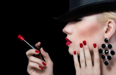 lip shine: Giovane e bella donna con labbra rosse e manicure su sfondo nero