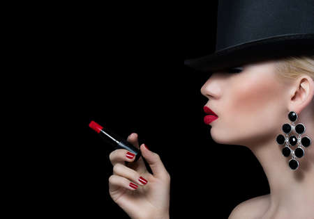 Beautiful blonde woman with cigarette and red lips on black background