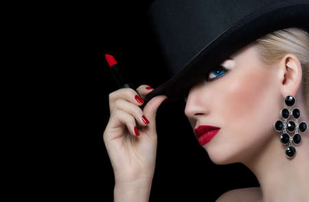 Beautiful girl in hat with red lipstick on black background photo
