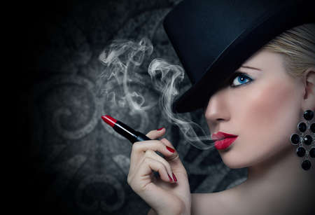Pretty blonde girl with cigarette and red lips Stock Photo