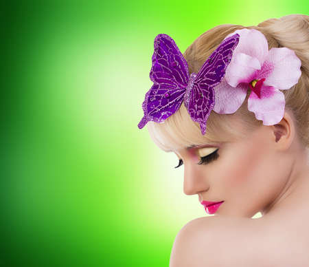 Beautiful blonde girl with orchid flower and butterfly on green background photo