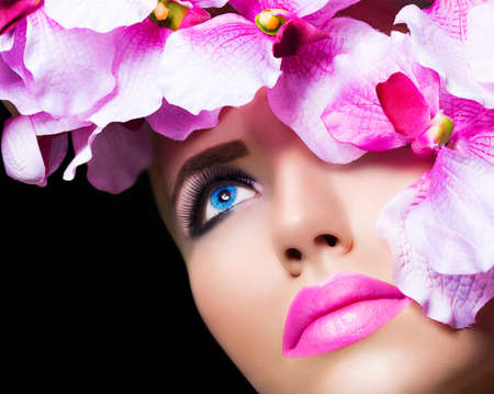 Beautiful girl with flowers and perfect makeup on black background photo
