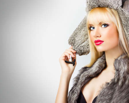 Beautiful blonde girl in fur hat on grey background photo