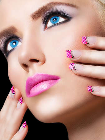 Beautiful blonde girl with pink lips and nails on black background Stock Photo