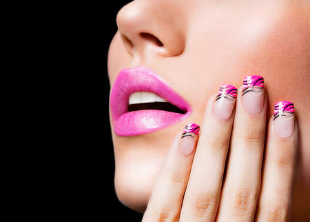Beautiful girl with pink lips and nails on black background photo