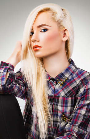 Beautiful blonde girl in shirt on grey background photo