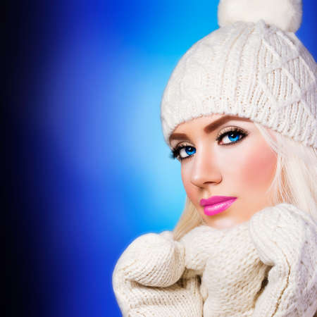 Beautiful blonde girl in winter hat on blue background photo